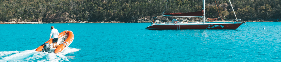 Siska, Sailing Whitsundays, tender over blue water.