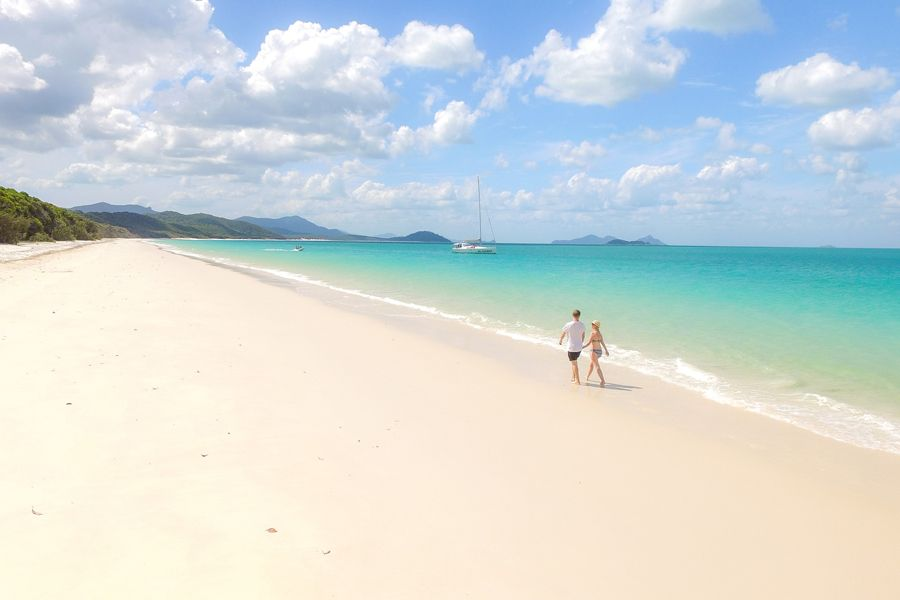 Couple walking along Whitehaven Beach